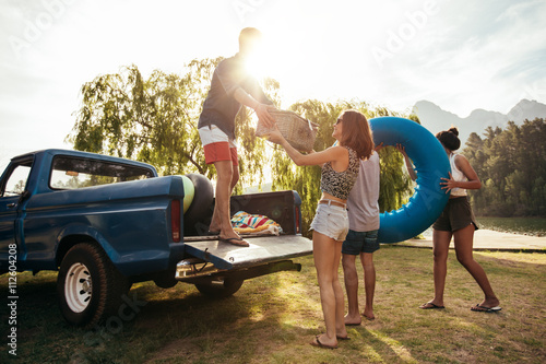 Obraz Young friends unloading pickup truck on camping trip - fototapety do salonu