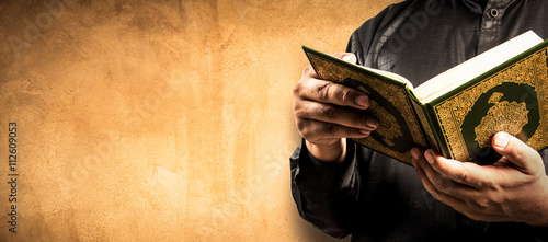 Photo  Koran in hand - holy book of Muslims ( public item of all muslims )