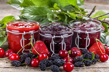 strawberry, cherry and mulberry jam on a rustic table