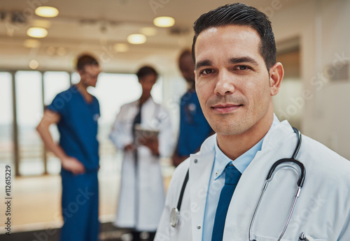 Male doctor with colleagues in background Poster