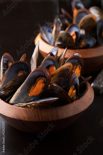 фотографія  Delicious mussels with fresh herbs in a pot