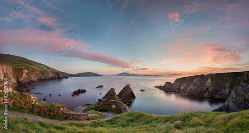 Fotografie, Obraz  Irish landscape with rocks and steep road to quay where a little ferry departs t