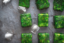 Cubes Of Frozen Spinach With Ice Cubes On The Stone Table Top View