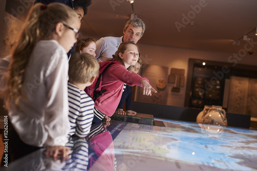 Photo  Pupils On School Field Trip To Museum Looking At Map