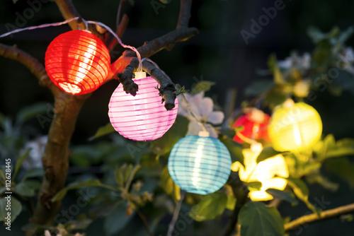 Fotobehang Tuin bunte Lampions am Abend im Garten