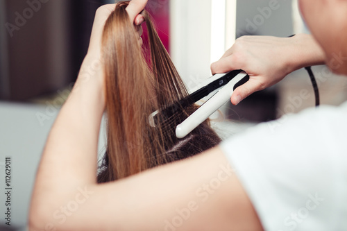 Hairstylist using a curling iron of a female client in a hairdressing salon, clo Slika na platnu