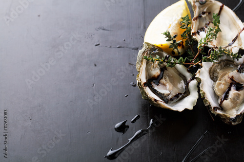 Photo  Fresh Oysters in shell with sauce and lemon