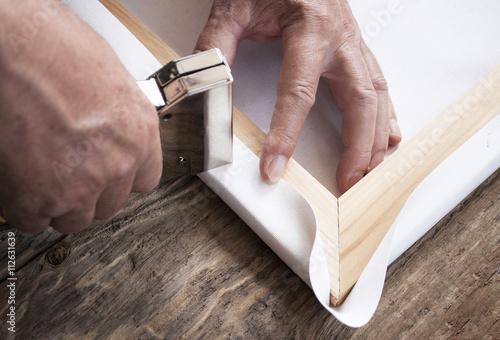 Fototapeta Rahmenbauer zieht Leinwand (Canvas) auf Keilrahmen mit Tacker auf