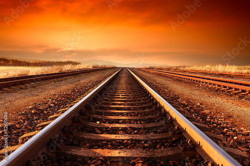 Wall Murals Railroad Train tracks goes to horizon in the majestic sunset.