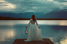 Woman Waiting With Lantern On A Pier