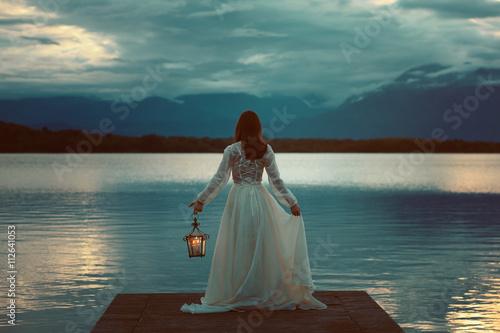 Obraz Woman waiting with lantern on a pier - fototapety do salonu