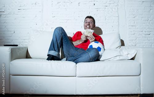 Fotografía  crazy man holding money and soccer ball watching football on tv internet online