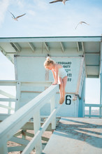 Young Girl Climbing On Fence At Beach