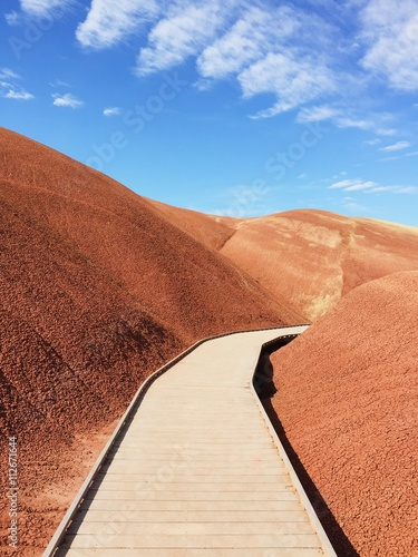 Coral Boardwalk winding through red sandhills with blue sky and clouds in the horizon