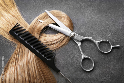 Stampa su Tela Hairdresser's scissors with comb and strand of blonde hair on grey background
