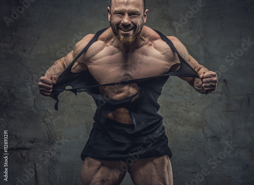 Huge bodybuilder rend his garments. Fototapeta