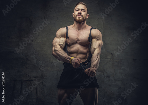 Huge bodybuilder rend his garments. Fotobehang