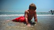 Slow motion of kid playing with sand while lying in the ocean