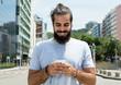 canvas print picture - Mann mit Vollbart im grauen Shirt schreibt Nachricht