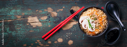 Fototapeta Asian noodles with vegetables and mushrooms, soy sauce, sticks on a dark background, top view with copy space  obraz