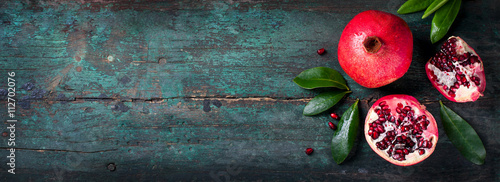 Fresh juicy pomegranate - whole and cut, with leaves on a wooden vintage background, top view, horizontal, with copy space