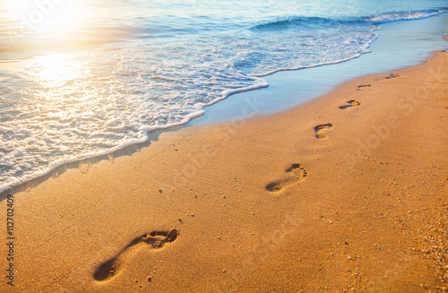 Foto-Leinwand - beach, wave and footprints at sunset time (von Alexander Ozerov)