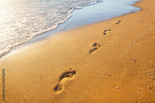 beach, wave and footprints at sunset time Canvas Print