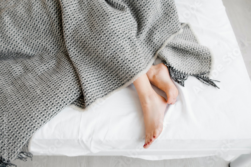 Photo  Female feet under blanket flat lay