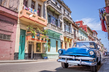Fototapeta Samochody Blue vintage classic american car in a colorful street of Havana, Cuba. Travel and tourism concept.