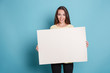 canvas print picture - Pretty young woman holding empty blank board over blue background