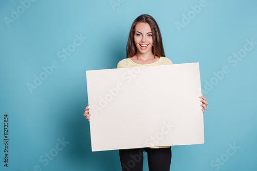 Fotografering  Pretty young woman holding empty blank board over blue background
