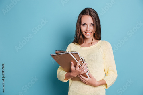 Fotografie, Tablou  Portrait of beautiful young brunette with notebooks