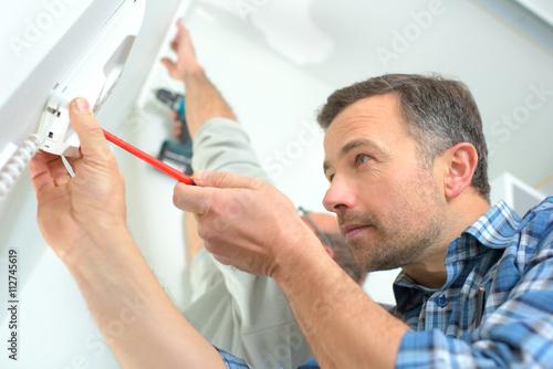 Fényképezés  Builder installing an intercom