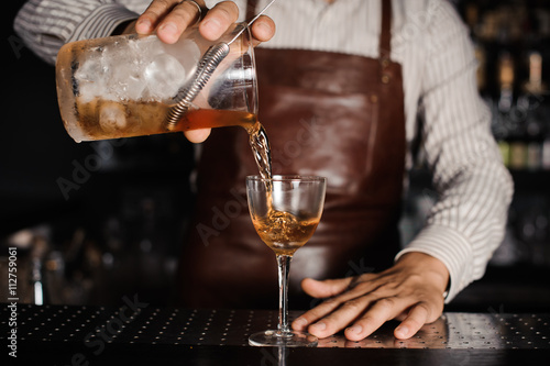 Foto  barman pouring alcoholic cocktail in glass