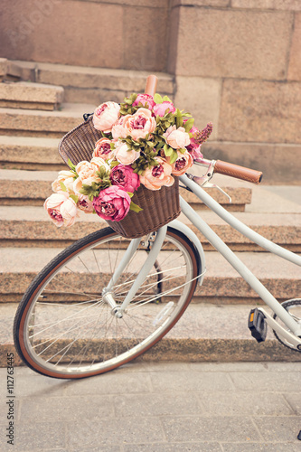 Fotobehang Fiets vintage girls bicyclewith flowers in basket