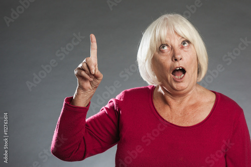 Photo  Female senior showing up, surprised. Horizontal portrait on gray