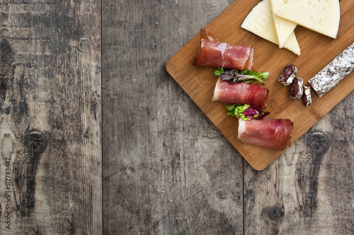 Foto  Spanish serrano ham, cheese and sausage on a rustic wooden background