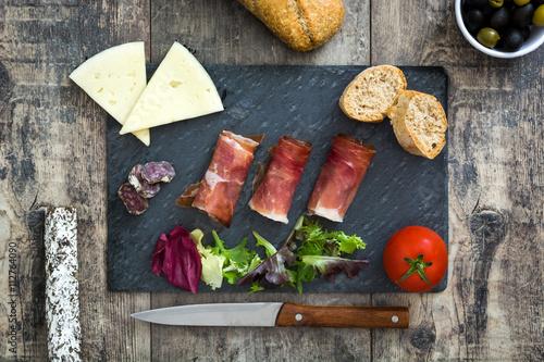 Fotomural  Español jamón serrano, queso y salchichas en la pizarra negro