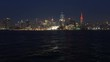 New York city skyline at night. City lights reflects on the water. Manhattan New York City