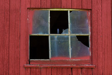 A Broken Window On Barn With Red Siding