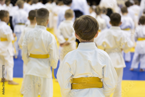 Children in kimono sitting on tatami on martial arts seminar. Selective focus on a boy