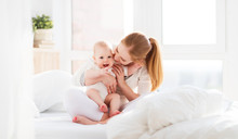 Happy Family Mother  With Baby Playing And Hug In Bed