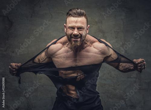 Obraz na plátně  Huge bodybuilder rend his garments.