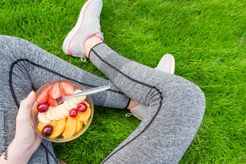 Foto op Canvas Kruidenierswinkel Young girl eating a fruit salad after a workout . Fitness and healthy lifestyle concept.