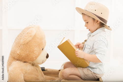 dde45a2caedc0 An adorable little girl in a safari hat and explorer clothes reading old  book sitting on