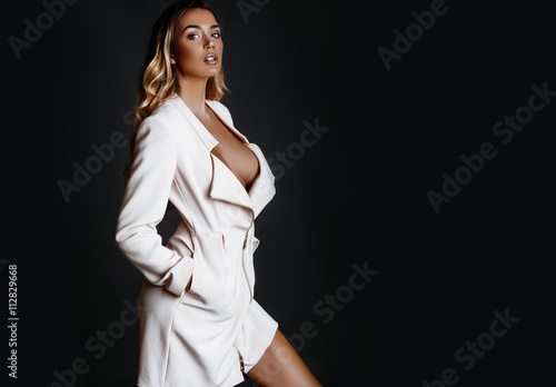 Fotografie, Tablou  Beautiful, sexy blonde girl with bronze tan in a white coat and beige shoes posing in a studio on a dark background