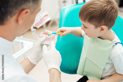 Dentist teaching little boy bruching teeth in dental clinic - 112836065
