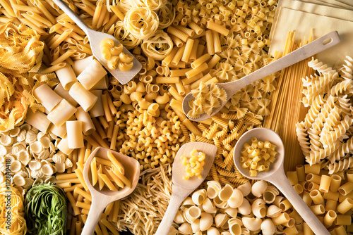 Fotografering fondo di pasta italiana mista con cucchiai di legno