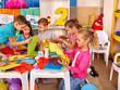 Group kids holding colored paper on table in kindergarten .Children learn together in kindergarten.