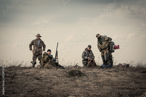 Foto op Aluminium Jacht Hunters standing together against sunset sky in rural field during hunting season